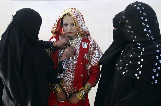A relative, left, adjusts the costume of a bride during a mass marriage of 162 Muslim couples in Ahmadabad, India, Sunday, March 3, 2013. Mass marriages in India are organized by social organizations primarily to help the economically backward families who cannot afford the high ceremony costs as well as the customary dowry and expensive gifts that are still prevalent in many communities. (Photo by Ajit Solanki/AP Photo/LaPresse)