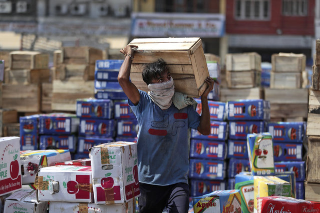 An Indian laborer wearing a mask carries boxes of apples at a wholesale market on the outskirts of Jammu, India, Wednesday, September 23, 2020. The nation of 1.3 billion people is expected to become the pandemic's worst-hit country within weeks, surpassing the United States. (Photo by Channi Anand/AP Photo)