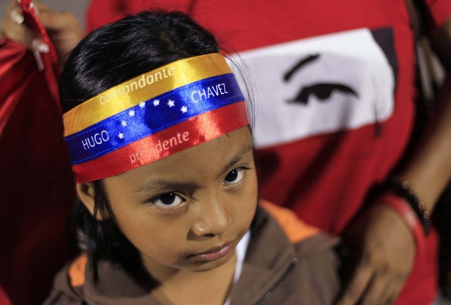 "A young supporter of Venezuela's President Hugo Chavez wears a headband that reads ""Commander Hugo Chavez, President"" while standing at a square in San Salvador March 5, 2013. Chavez died on Tuesday after a two-year battle with cancer, ending 14 years of tumultuous rule that made the socialist leader a hero for the poor but a hate figure to his opponents. (Photo by Ulises Rodriguez/Reuters)"