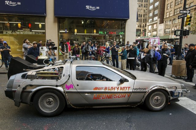 """Pedestrians stop to look at and photograph a DeLorean Motor Company DMC-12, customized to look identical to the car used in the film """"Back to the Future Part II"""", and that will be part of a Lyft promotion, in New York October 21, 2015. Today marks the day that the movie's main character, Marty McFly, travelled to the future in the 1989 """"Back to the Future"""" sequel. (Photo by Lucas Jackson/Reuters)"""
