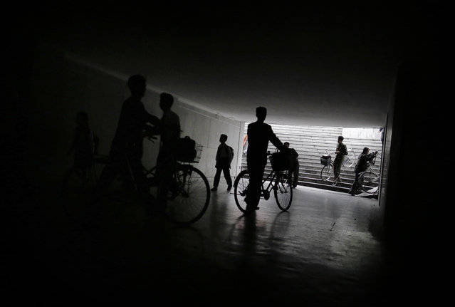 North Korean men are seen in silhouette as they push their bicycles, while a boy makes his way to school in an underpass on Wednesday, September 28, 2016, in Pyongyang, North Korea. (Photo by Wong Maye-E/AP Photo)