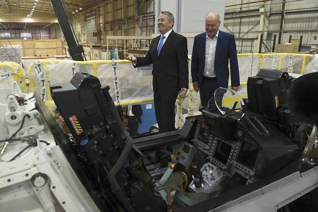 Managing Director Tony Birmingham (R) shows International Trade Secretary Liam Fox a Euro Fighter simulator, during a visit to EDM Ltd in Newton Heath, Manchester, Britain September 29, 2016. (Photo by Anthony Devlin/Reuters)