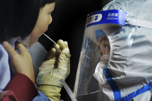 A medical staff takes a swab from a child near a residential area in Qingdao in east China's Shandong province on Tuesday, October 13, 2020. A hospital president and the director of the health commission in the northern Chinese city of Qingdao have been fired after China's latest coronavirus outbreak, authorities said Thursday, Oct. 15, 2020. (Photo by Chinatopix via AP Photo)