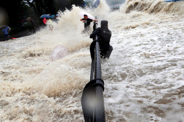 A paramilitary policeman holds onto a fence as tourists dodge tidal waves increased under the influence of Typhoon Dujuan, at the bank of Qiantang river, in Hangzhou, Zhejiang province, September 29, 2015. (Photo by Reuters/Stringer)