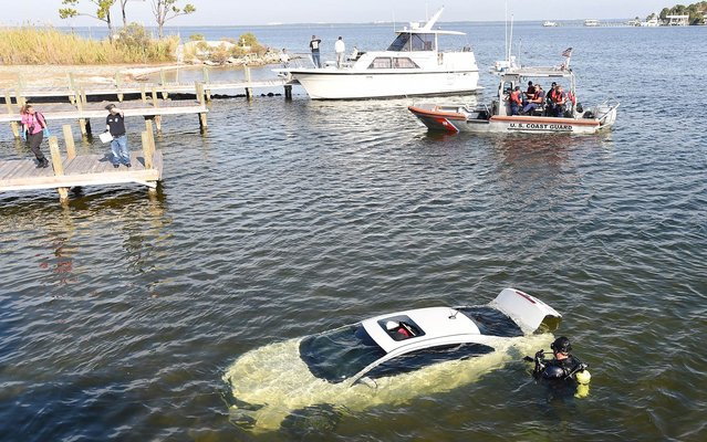 A member of the Okaloosa County Sheriff Office dive team examines a submerged vehicle near the boat ramp in Joe's Bayou in Destin, Fla. on Friday, December 5, 2014. The car contained the body of an adult, according to the Sheriff's Office. Officials said they would release more details of the incident following further investigation. (Photo by Nick Tomecek/AP Photo/Northwest Florida Daily News)