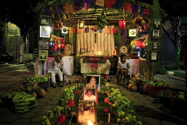"""People gather around a family altar as they celebrate """"Los Canchules"""" in Nahuizalco November 1, 2015. People remember their deceased relatives and friends during All Saints Day by preparing altars and sharing food with all visitors, prior to the Day Of the Dead. (Photo by Jose Cabezas/Reuters)"""