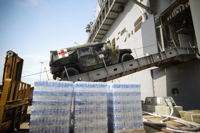 A medical vehicle attached to the 24th Marine Expeditionary Unit (24th MEU), drives aboard the amphibious assault ship USS Iwo Jima (LHD 7) during an onload of more than 500 Marines from the 24th Marine Expeditionary Unit and nearly 300 pallets of supplies, awaiting further tasking at Naval Station Norfolk, Virginia, U.S., on October 7, 2016 as Hurricane Matthew left flooding and wind damage in Florida before moving north to soak coastal Georgia and the Carolinas. (Photo by Courtesy Jess E. Toner/Reuters/U.S. Navy)