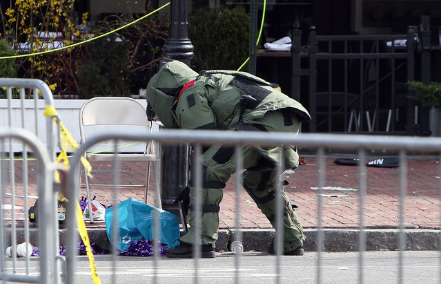 A member of the bomb squad investigates a suspicious item on the road near Kenmore Square after two bombs exploded during the 117th Boston Marathon on April 15, 2013 in Boston, Massachusetts. (Photo by Alex Trautwig)