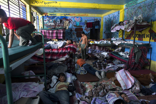 "In this July 17, 2014 file photo, boys watch television in their room at The Great Family group home in Zamora, Mexico. After a police raid on the refuse-strewn group home, residents of the shelter told authorities that some employees beat residents, fed them rotting food or locked them in a tiny ""punishment"" room. Shelter residents were still being kept at the home while officials look for places to transfer them. (Photo by Rebecca Blackwell/AP Photo)"