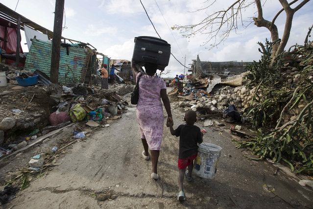 A woman walks to a shelter with her son as they leave after their home was destroyed by Hurricane Matthew in Jeremie, Haiti on Sunday, October 9, 2016. Jeremie appears to be the epicenter of the country's growing humanitarian crisis in the wake of the storm. (Photo by Dieu Nalio Chery/AP Photo)