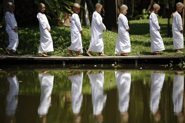 Novice nuns walk in the garden of the Sathira-Dhammasathan Buddhist meditation centre in Bangkok April 21, 2013. A group of Thai girls are choosing to spend part of their school holidays as Buddhist nuns, down to having their heads shaven at the meditation centre. The centre, founded in 1987, is a learning community for peace and harmony that has programs open to people regardless of age and gender. (Photo by Damir Sagolj/Reuters)