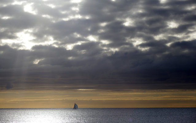 A boat sails on the Mediterranean sea at Cagnes sur Mer, near Nice, southeastern France, Sunday, December 7, 2014. The temperature rose to 18 degrees cels ius (64 fahrenheit). (Photo by Lionel Cironneau/AP Photo)