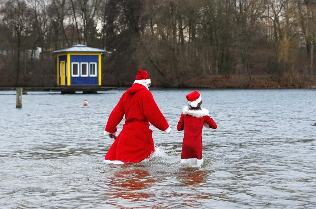"""Members of the ice swimming club """"Berliner Seehunde"""" (Berlin Seals) take a dip in the Orankesee lake in Berlin as part of their traditional Christmas ice swimming session, December 25, 2014. (Photo by Fabrizio Bensch/Reuters)"""