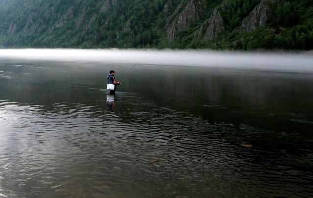A man fishes in the waters of the Yenisei river in the Siberian Taiga district outside Krasnoyarsk, Russia June 16, 2016. (Photo by Ilya Naymushin/Reuters)
