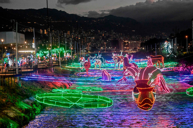 View of Christmas illuminated decorations over the Medellin river in Medellin, Colombia on December 3, 2020. (Photo by Joaquín Sarmiento/AFP Photo)