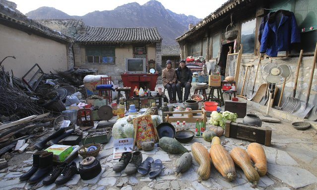 A couple with their belongings and vegetables in Hebei Huailai county. (Photo by Ma Hongjie)