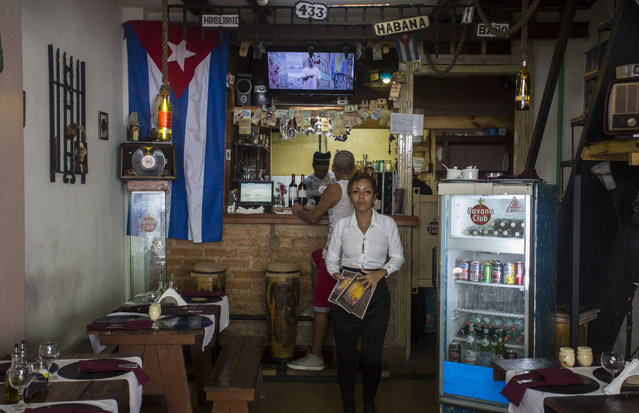 A waitress at a private restaurant waits for customers in Havana, Cuba, Tuesday, October 3, 2017. (Photo by Desmond Boylan/AP Photo)
