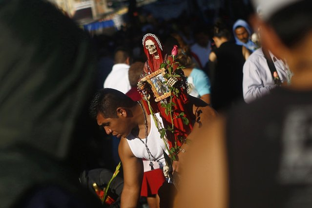 A follower carries a sculpture of La Santa Muerte (The Saint of Death), a cult figure often depicted as a skeletal grim reaper, as he buys souvenirs near the saint's altar at Tepito neighborhood, in Mexico City January 1, 2015. (Photo by Edgard Garrido/Reuters)