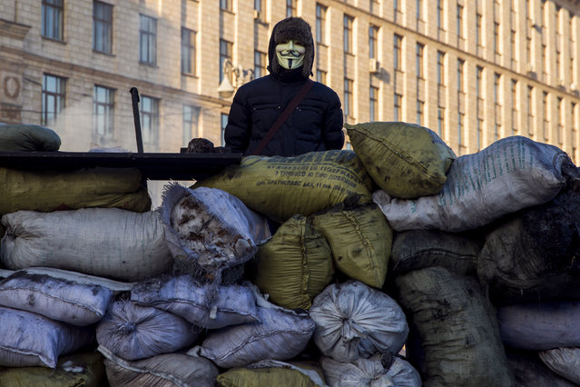 Ukraine: An anti-government protester wears a Guy Fawkes mask as he stands on a barricade in Kiev, February 3, 2014. (Photo by Thomas Peter/Reuters)