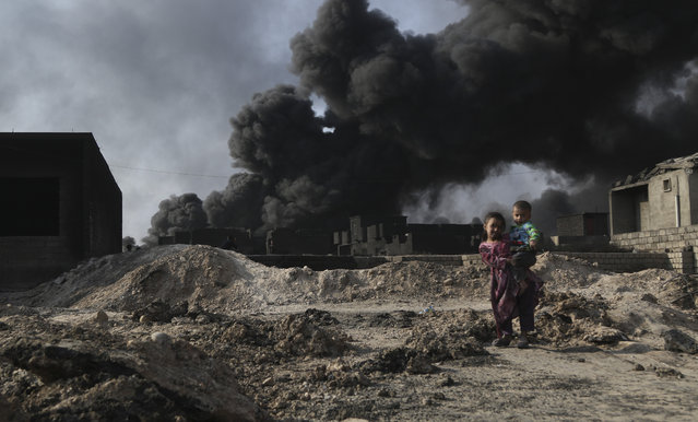 A girl holds her brother in her arm as black smoke rises after an oil well set on fire in the center of al-Kayyara town to the south of Daesh terror organization-held Mosul in Iraq on October 25, 2016. The oil well in the center of al-Kayyara town, which was set alight by retreating Daesh militants in advance of the Iraqi army's takeover of the town on August 24, 2016 has still not entirely been put out. The raw petrol which is still alight is creating black clouds above the city. The residents and wildlife beneath this polluting smoke cloud may find their health at risk. The effects of the fire in the town center on unprotected civilians' health can easily be seen on the hands and faces of children playing on the street. (Photo by dris Okuducu/Anadolu Agency/Getty Images)