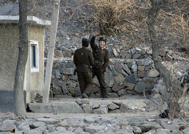 A North Korean soldier waves to a Chinese tourist boat on the banks of Yalu River near the North Korean town of Sinuiju, opposite the Chinese border city of Dandong, January 7, 2011. (Photo by Reuters/Stringer)