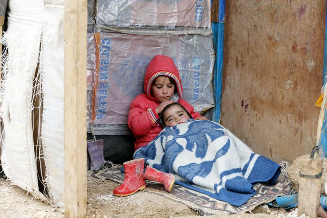 A Syrian refugee girl sits with her brother at a makeshift settlement in Bar Elias in the Bekaa valley January 5, 2015. (Photo by Mohamed Azakir/Reuters)
