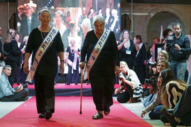 Judith Rosenzweig, 81, (R) and Rivka Shtanger, 74, (L) both Holocaust survivors, walk on a runway during a beauty contest for survivors of the Nazi genocide in the northern Israeli city of Haifa, November 24, 2015. (Photo by Amir Cohen/Reuters)