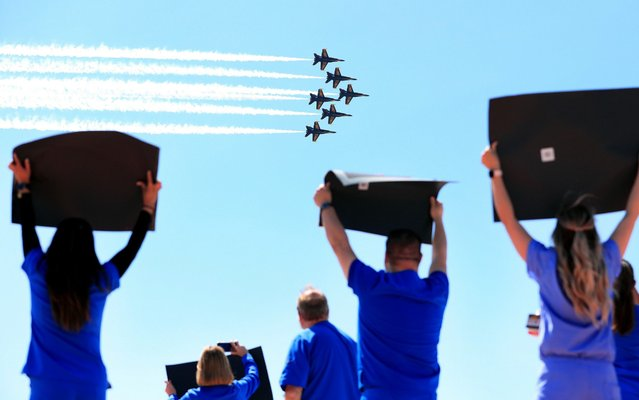 Hospital staff, including nurses, doctors, and administrators, cheer and look on as the United States Navy Blue Angels pass over Medical City Dallas on May 06, 2020 in Dallas, Texas. The flyover across the Dallas-Fort Worth area was conducted as a show of support for health care workers and first responders fighting the coronavirus (COVID-19) pandemic. (Photo by Tom Pennington/Getty Images)