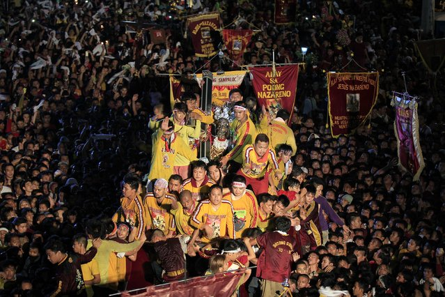 Devotees welcome the Black Nazarene as it is pulled on a carriage toward the entrance of a Catholic church after a 19-hour procession in Manila January 10, 2015. (Photo by Romeo Ranoco/Reuters)