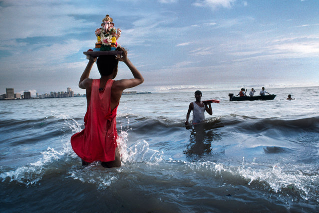 A devotee carries a statue of Lord Ganesh into the Arabian Sea during an immersion ritual off Chowpatty beach. Mumbai, 1993. (Photo by Steve McCurry)