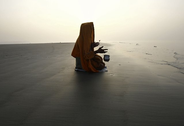 "A ""Sadhu"", or a Hindu holy man, offers prayers after taking a dip at the confluence of the river Ganges and the Bay of Bengal, ahead of the Makar Sankranti festival at Sagar Island, south of Kolkata January 13, 2015. (Photo by Rupak De Chowdhuri/Reuters)"