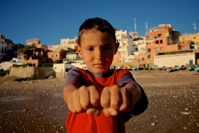 """""""Left or right?"""" I was taking some shots on the beach of Taghazout, Morocco, when this little guy came up to me asking in what hand he was holding a coin. After playing along I asked if I could take his picture. (Photo and caption by Thomas Pieters/National Geographic Traveler Photo Contest)"""