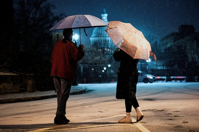 Women watch the snow fall on Capitol Hill in Washington, U.S., January 25, 2021. (Photo by Al Drago/Reuters)