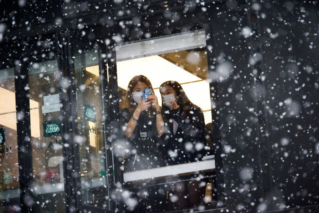 A woman takes photographs of falling snow from a window during a heavy snowfall, amid the coronavirus disease (COVID-19) pandemic in Seoul, South Korea, January 12, 2021. (Photo by Kim Hong-Ji/Reuters)