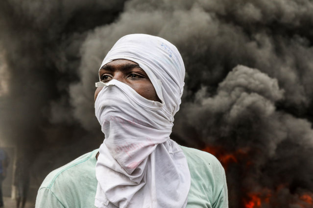 Opposition protesters burn tires during a demonstration, calling for the departure of President Jovenel Moise, as they march through the streets of Port-au-Prince on November 18, 2020. (Photo by Valerie Baeriswyl/AFP Photo)
