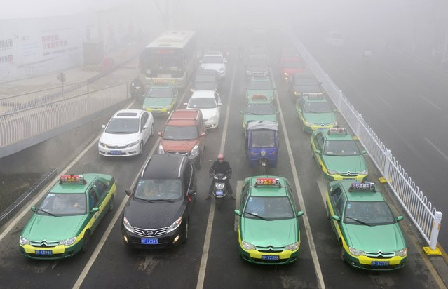 An electric bicycle stops among cars while waiting at a traffic light on a hazy day in Xiangyang, Hubei province January 16, 2015. (Photo by Reuters/Stringer)