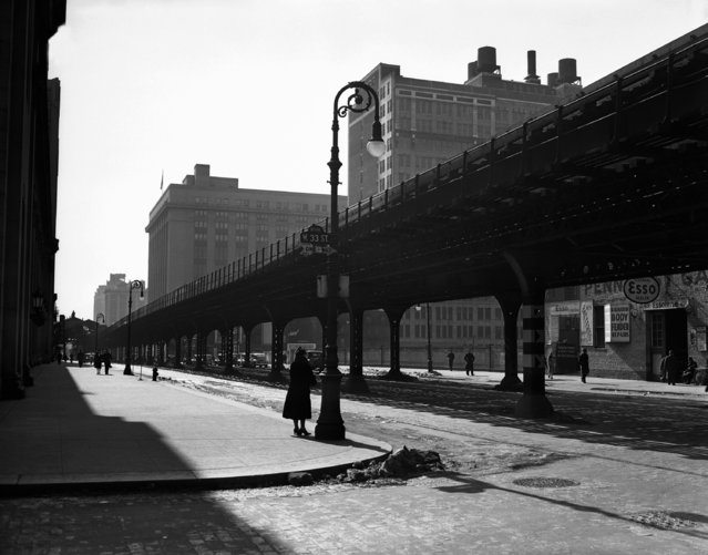 """The Ninth Avenue """"El"""", or elevated, tracks are seen looking south at 33rd Street in New York, February 22, 1940. The transit commission authorized condemnation of the structure. (Photo by AP Photo)"""