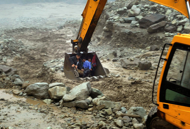 An excavator moves villagers away from a flooded area during heavy rainfall in Yingxiu, Wenchuan county, Sichuan province, July 10, 2013. More than 300 hundred people were evacuated in Yingxiu after roads connecting the township to the outside were cut off by floods and landslides. (Photo by Reuters/Stringer)