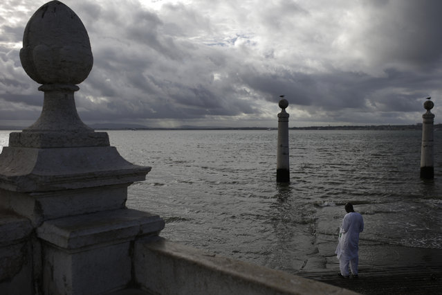 A muslim man prays at the Cais das Colunas dock by the Tagus riverbank, in Lisbon, Monday, November 3, 2014. (Photo by Francisco Seco/AP Photo)