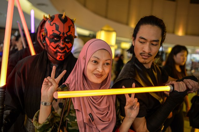 """A Malaysian Muslim woman (C) poses for pictures with members of Malaysia's Star Wars Fan Club dressed as various characters before watching """"Star Wars: The Force Awakens"""" at a cinema in Subang, outside Kuala Lumpur on December 17, 2015. (Photo by Mohd Rasfan/AFP Photo)"""