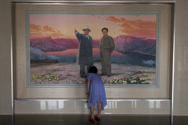 In this Friday, June 21, 2013 photo, a woman arranges flowers in front of a painting depicting the late leaders Kim Il Sung, left, and Kim Jong Il at the lobby of a hotel in Haeju city, South Hwanghae Province, North Korea. (Photo by Alexander F. Yuan/AP Photo)