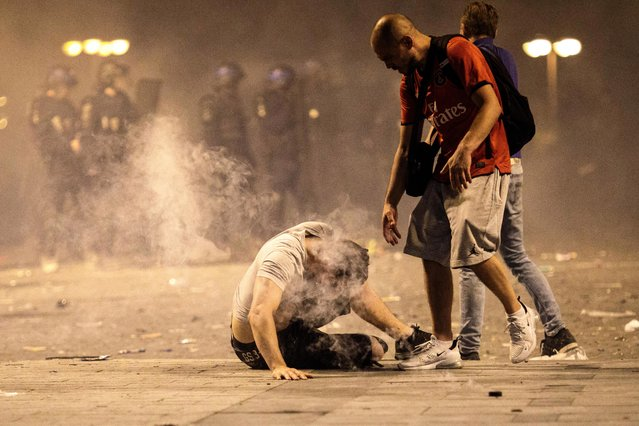 A man falls to the floor after inhaling tear gas as French football fans clash with police following celebrations around the Arc de Triomph after France's victory against Croatia in the World Cup Final on July 15, 2018 in Paris, France. France beat Croatia 4-2 in the World Cup Final played at Moscow's Luzhniki Stadium today. (Photo by Jack Taylor/Getty Images)