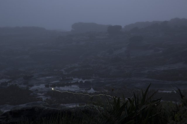 A Pemon indigenous porter holds a light as he walks on the top of Roraima Mount, near Venezuela's border with Brazil January 16, 2015. (Photo by Carlos Garcia Rawlins/Reuters)