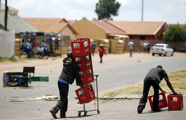 Locals carry soft drinks in crates after looting them from a shop, believed to be owned by a foreigner, during service delivery protests in Mohlakeng, west of Johannesburg, February 4, 2015. (Photo by Siphiwe Sibeko/Reuters)