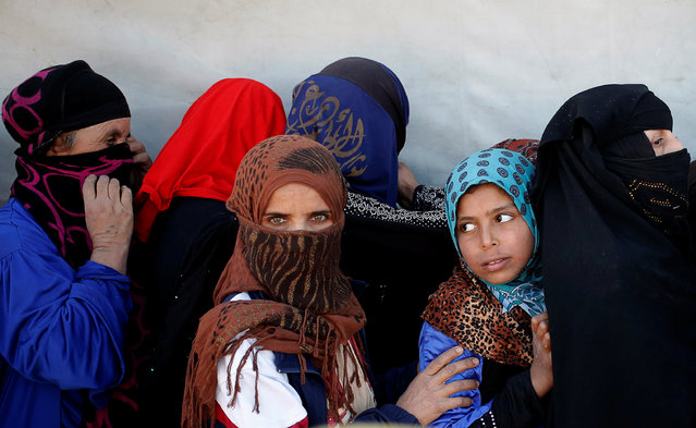 Women wait for food donated by an Iraqi government organisation at the outskirts of Mosul, Iraq, November 20, 2016. (Photo by Goran Tomasevic/Reuters)