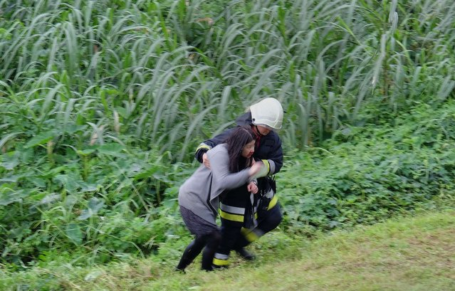 An injured passenger (L) is escorted by emergency personnel up the river bank after a TransAsia ATR 72-600 turboprop plane crash-landed into the Keelung river outside Taiwan's capital Taipei in New Taipei City on February 4, 2015. The low-flying passenger plane, TransAsia Flight GE235 with 58 people on board, clipped a road bridge and plunged into the river outside Taiwan's capital with at least nine feared dead and many trapped inside. (Photo by Sam Yeh/AFP Photo)