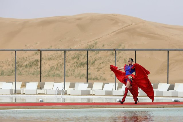 A model performs in Mongolia costumes near a swimming pool in Xiangshawan Desert, also called Sounding Sand Desert on July 18, 2013 in Ordos of Inner Mongolia Autonomous Region, China. Xiangshawan is China's famous tourist resort in the desert. It is located along the middle section of Kubuqi Desert on the south tip of Dalate League under Ordos City. Sliding down from the 110-metre-high, 45-degree sand hill, running a course of 200 metres, the sands produce the sound of automobile engines, a natural phenomenon that nobody can explain. (Photo by Feng Li/Getty Images)