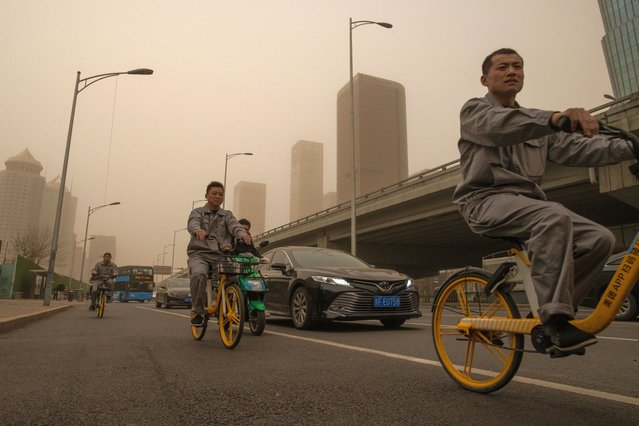 People ride bicycles in the Central Business District (CBD) area amid a sandstorm in Beijing, China, 28 March 2021. A new sandstorm hit Beijing on 28 March as the city was already in the grip of high air pollution levels. (Photo by Roman Pilipey/EPA/EFE)
