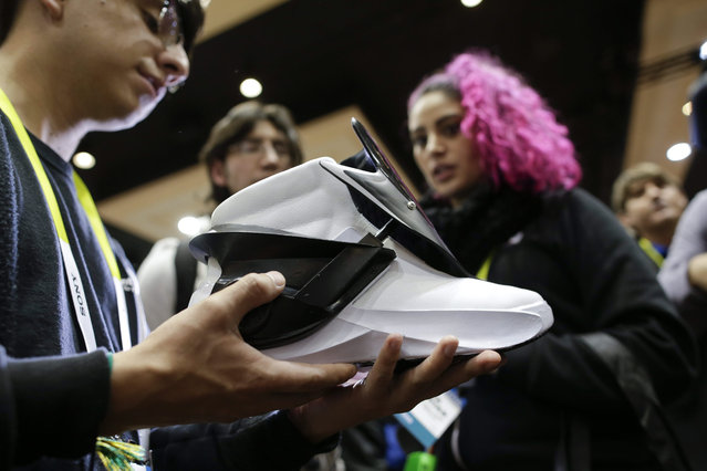 A man holds a Digitsole Smart Shoe at CES Unveiled, a media preview event for CES International, Monday, January 4, 2016, in Las Vegas. The Smart Shoe can warm your feet, track your steps and light your way and tighten themselves. (Photo by Gregory Bull/AP Photo)