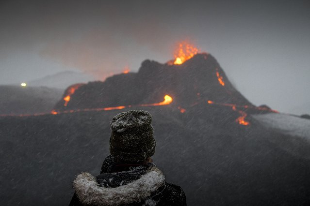 A person watches as lava flows from an eruption of a volcano on the Reykjanes Peninsula in southwestern Iceland on Wednesday, March 24, 2021. Iceland's latest volcano eruption is quickly attracting crowds of people hoping to get close to the gentle lava flows. The eruption in Geldingadalur, near Iceland's capital Reykjavik, is not seen as a threat to nearby towns and the slow flows mean people can get close to action without too much harm. (Photo by Marco Di Marco/AP Photo)